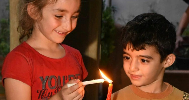 Os filhos de Steven acendem velas na celebração do Dia da Cruz em Qaraqosh, no Iraque